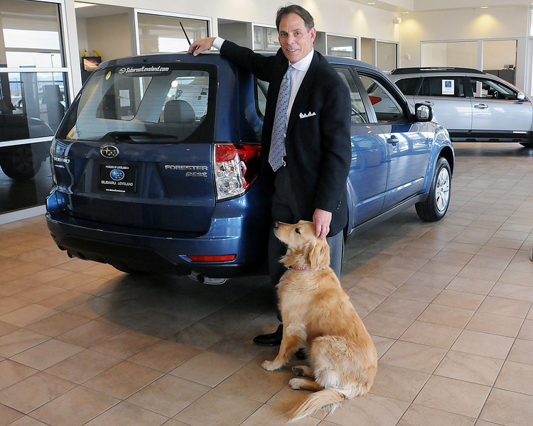 Joe Gebhardt, owner of Davidson-Gebhardt Auto Group, 3880 Test Circle, and one of the dealership's greeter dogs named Chloe stand Tuesday, March 30, 2010 next to a 2010 Subaru Forester which has the Partial Zero Emission Vehicle classification. The dealership will have the Forester along with a Chevrolet FlexFuel and a diesel pickup on display in downtown Loveland Thursday as part of the 2nd Annual Green Car Convoy, a statewide tour of alternative fuel and hybrid vehicles.