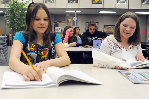 Conrad Ball Middle School sixth grader MaKaylee Wahl, 11, left, and eighth grader Lizzy Trotter fill out a workbook while participating in the Learning Together after school program with others Tuesday in the school's library.