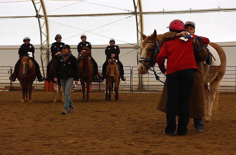 Jessica Burton, red, hugs volunteer trainer, Monica Rasmussen who has been teaching her the ropes of handling the horse behind them, Miss Molly. Program Director, Tamara Merritt, smiles at seeing Burton and 3 other students complete the 8-week program, Mar 5, with the help of the Mounted Patrol behind her.