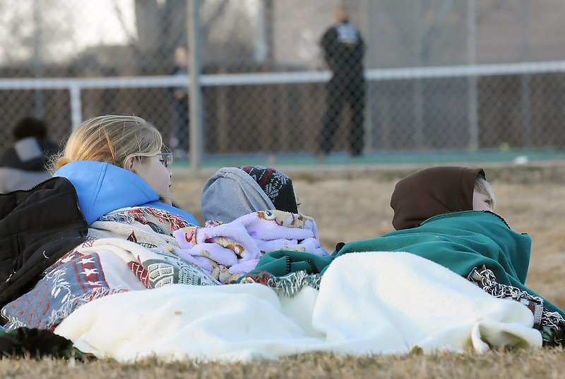 Loveland residents and siblings Miranda Sheets, 13, left, Jeremiah Sheets, 6, and Isaac Sheets, 12, huddle together under some blankets to ward off the cold as they watch a tennis tournament between Thompson Valley High School and Greeley West on Thursday at TVHS.