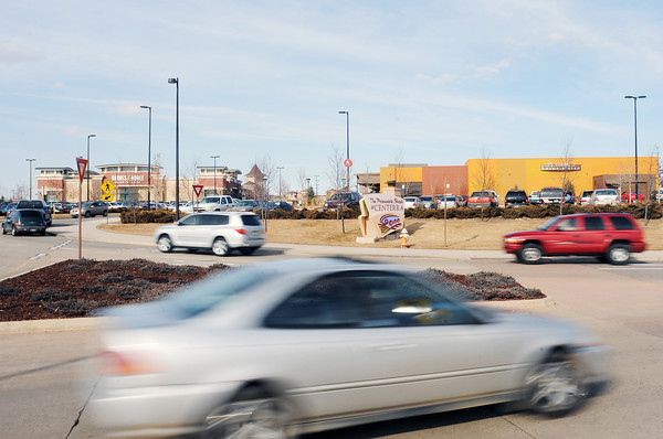 Vehicles stream in and out of the Promenade Shops at Centerra on Saturday afternoon at the roundabout located at the shopping center's southwest entrance.