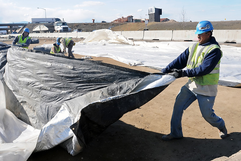 Jesús Roman, right, battles the wind as he and other workers from Jalisco Internationa, Inc. remove tarps Tuesday off Crossroads Blvd., just east of Interstate 25 that were keeping the ground warm in preparation for paving as part of the construction project at the interchange. Fans heading to Jeff Dunham's sold-out show at the Budweiser Events Center Thursday night will need to take an alternate route to the venue as the Crossroads Blvd. exit off of northbound I-25 will be closed.
