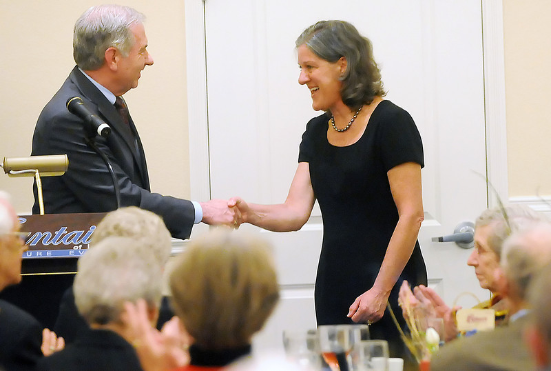 Moofie Miller, right, is congratulated by Norm Rehme after being named Rotarian of the Year on Tuesday night during the Rotary Club of Loveland's 90th Anniversary Celebration at The Fountains of Loveland.