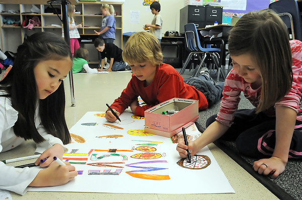 "Coyote Ridge Elementary School second graders Rachel Blecke, 8, left, Griffin Stoddart, 7, and Zoe Fiedler, 7, work on a poster for their restaurant business called ""The East Moon"" during class Friday."