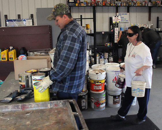 Hazardous waste technician Paul Seevers, left, assists Loveland resident Mary Ann Jakabosky as she drops off old paint at the Larimer County Landfill's Household Hazardous Wast Facility on Thursday.
