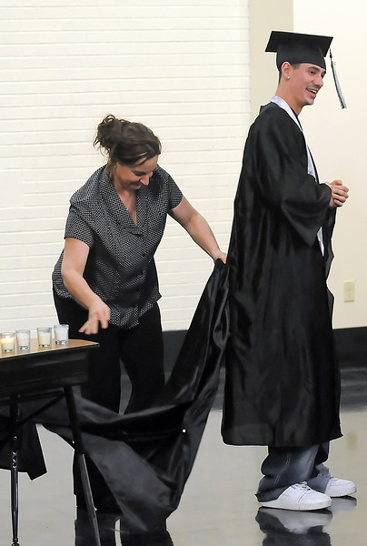 Ferguson High School science teacher Cathy Beach attaches a second gown to Kobi Vargas' graduation gown during the school's third quarter graduation on Thursday, March 11, 2010.