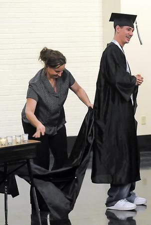 Ferguson High School science teacher Cathy Beach attaches a second gown to Kobi Vargas' graduation gown during the school's third quarter graduation on Thursday, March 11, 2010.