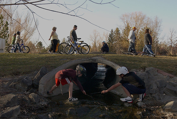 "Mother Karen Brock kneels by the far side of a tunnel in Bensen Sculpture Park, racing twigs down current towards Tyler Frisch, left, and Ian Brock, right.  While the boys play ""Pooh Sticks"", other passersby wander through the park, left to right, Maegen Carr, Gabrielle Wells, Helen Fischer, Steven Fischer, Randal Kauffman, Carol Sarlo, and Virginia Kauffman."