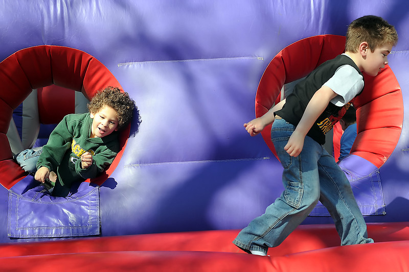 Isiah Shavers, 5, left, and Charles Troncoso, 5, climb out the back of an inflatable castle while playing together during the City of Loveland's Colorado Children's Day events in downtown Loveland on Wednesday, March 3, 2010.