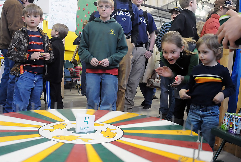 Three -year-old Merick Fisbeck, right, and his sister, Ali Hensem, 11, watch the wheel spin and cheer for it to stop on a fish at the Rocky Ridge 4-H Club's Wheel of Fortune booth Saturday during the 4-H Carnival and Crafts Show at The Ranch. Waiting their turn to spin the wheel are Braden Bensley, 7, left, of LaPorte and Loveland resident Cody Morgan, 11.