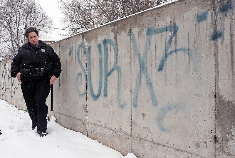 Loveland Police Officer Tammy Fisher stands Friday next to some sureño gang graffiti spraypainted on a cement wall in south Loveland.