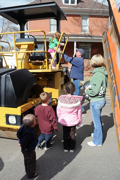Youngsters wait in line to climb aboard a steel drum roller as 5-year-old Autumn Wilhoit, back left, is helped down by Greg Sendek during Colorado Children's Day in downtown Loveland on March 2, 2011.