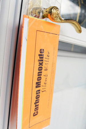 A packet containing information on carbon monoxide poisoning hangs from a handle on the front door of a home in Windsor after volunteers from the Loren Project made a visit Saturday during their door-to-door campaign to educate residents about the dangers of carbon monoxide.