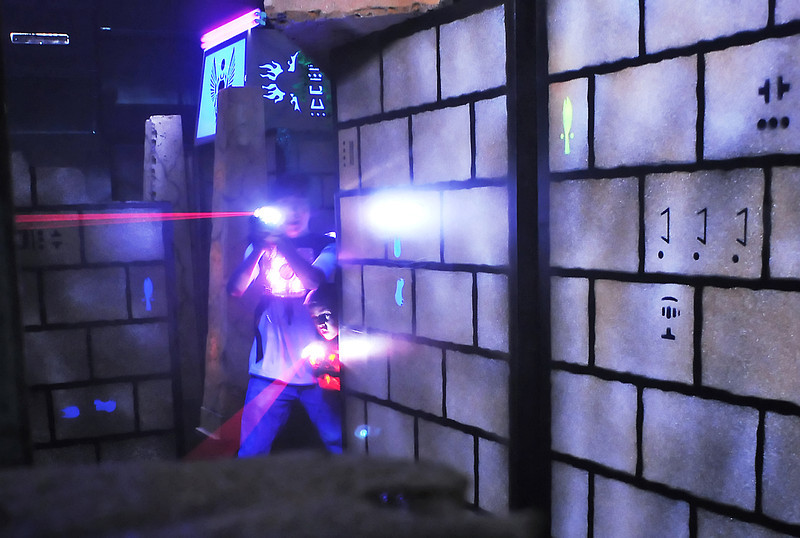 Logan Houseman, 14, left, and Zach Rechkemmer, 7, fire their lasers as they team up during a game Thursday evening at Loveland Laser Tag Fun Center located at 401 Denver Ave. in Loveland.