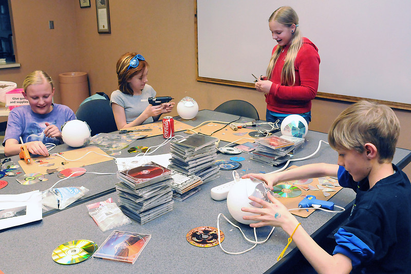 Youngsters construct disco balls using foam balls and discarded CDs during an activity Wednesday at the Loveland Public Library celebrating Teen Tech Week. From left are Alia Jackson, 12, Sammi Martinez, 12, Laura Marsh, 13, and Brandon Bouchard, 11.