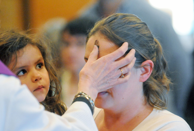 Four-year-old Abbigail Florez-Wright looks on as her mother, Andrea Wright, has an ashen cross marked on her forehead by Pastor Susan Candea on Wednesday at King of Glory Lutheran Church, 2919 N. Wilson Ave., during their Ash Wednesday service.