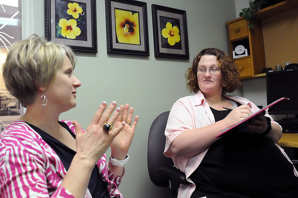 Healthy Beginnings care coordinator Katy Kupec, left, assists Danielle Reinert, who is due to have a baby this week, as she fills out preliminary paperwork for the new baby's birth certificate.