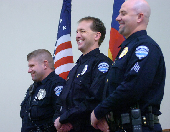Loveland Police officer Tim Yunger, left, officer Justin Lorenzen, center, and Sgt. Jeff Fisher smile as Chief Luke Hecker, not pictured, tells them how proud he is of them for their efforts busting burglars. The three were honored with Meritorious Service Awards Wednesday afternoon at the Loveland Police Department.