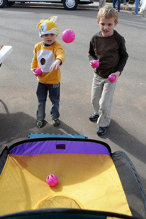 Cameron Lynn, 5, left, and his brother, Duncan Lynn, 7, shoot baskets while playing together in downtown Loveland at the Teaching Tree Early Childhood Learning Center booth as part of Colorado Children's Day activities on March 2, 2011.