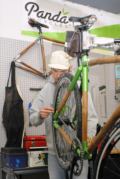 Panda Bicycles frame builder Kameron Moore trues the rear wheel of one of the company's bamboo-framed bicycles in the production area of the Fort Collins business.