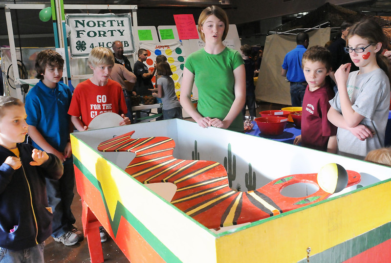 "Eleven-year-old Mitchell Leach, third from left, tries his hand at the Berthoud Highlanders 4-H Club's ""Snakes Alive"" game during the annual 4-H Carnival on Saturday at The Ranch. From left around the game are Sam Johnson, 6, Jake Pollema, 12, Mitchell, Meghan Conlon, 14, Kyle Conlon, 9, and Cara Conlon, 11."