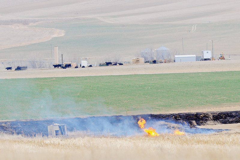 Smoke and flames rise from a controlled agricultural burn Friday afternoon in an irrigation ditch southwest of Johnstown.