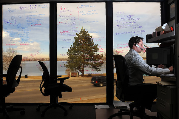 Madwire Media chief operating officer J.B. Kellogg works at his computer in the executive office of the Loveland business on Wednesday in front windows that have planning ideas written on them with dry erase markers.