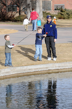 Trevan Coberly, 4, left, and his brother, Caden Coberly, 6, try their hands at casting fishing poles with assistance from Aimee Ryel of the Colorado Division of Wildlife at Foote Lagoon while participating in Colorado Children's Day activities on March 2, 2011.