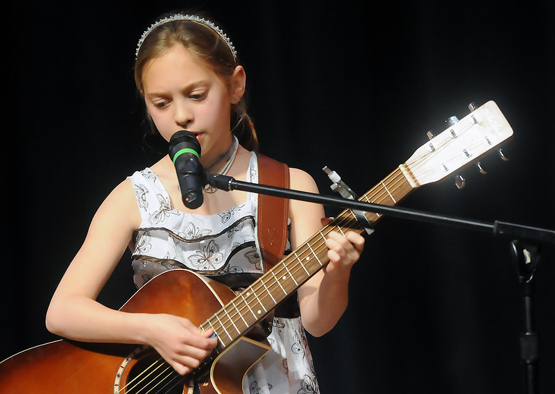 "Nine-year-old Taryn Johnson plays guitar and sings the song ""Kiss Me"" by Sixpence None the Richer while onstage during Stars of Tomorrow on Saturday, March 12, 2010 at Thompson Valley High School's Roberta L. Price Auditorium."