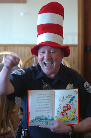 """Loveland Police Officer Dave Sloat weaves a safety lesson into the story as he reads """"The Cat in the Hat"""" for children from Trinity Lutheran Preschool."""