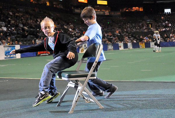 Loveland residents Andrew Nash, 10, left, and Micah Payton, 8, are the last two competitors in a game of musical chairs during a timeout of the Colorado Ice football game against the Wyoming Cavalry on Sunday at the Budweiser Events Center. Andrew edged out Michah for the win and was awarded a Colorado Ice sweatshirt for his effort.