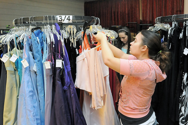 Rebecca Meuret, front, and Thompson Valley High School senior Amanda Richins, 17, sort through racks of dresses Wednesday afternoon at Loveland Wedding Center, 680 E. Eisenhower Blvd., where volunteers were setting up the upcoming Fairy Godmother Project. The project accepts donated dresses and also men's suits and then sells them to teens to wear to prom. When customers find a outfit they like they're asked to donate whatever amount of money they can before taking it home. For more information about the project or donation dropoff locations call Dee Valdez at (970) 308-1062. Valdez said they especially need donations of any men's suits or formal wear and plus sizes in women's dresses.