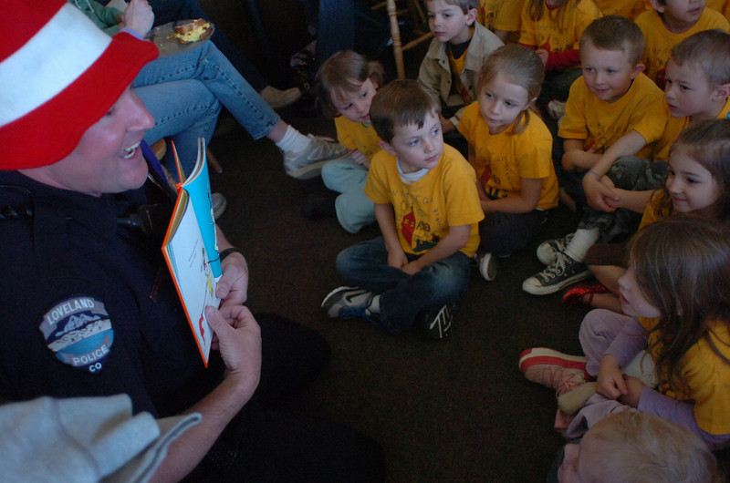 "Children from Trinity Lutheran Preschool listen as Loveland Police Officer Dave Sloat reads ""Green Eggs and Ham"" after the kids ate green eggs and ham for breakfast."