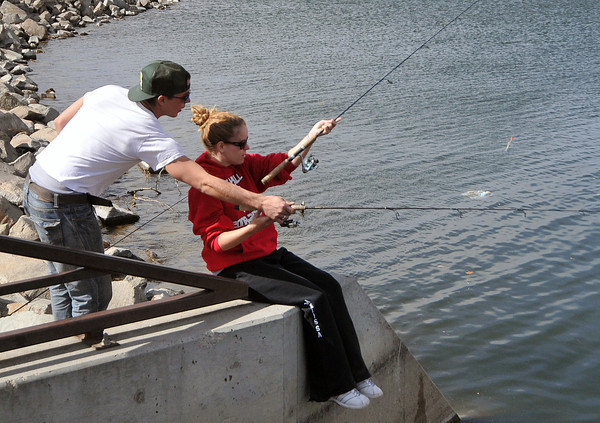 """031812_fishing-MN.jpg Landon Peppel and Melissa Brashers of Castle Rock fish Sunday afternoon from the bridge off of Eisenhower Boulevard on Lake Loveland's southern shore. The couple Saturday caught between 20-25 perch, Peppel said, enough to make a meal. Once the weather warms up this spring, the duo will be out fishing every weekend. In the meantime, Peppel said, """"It's nice to get wind and colder weather to keep the people away."""" (Photo by Madeline Novey)"""