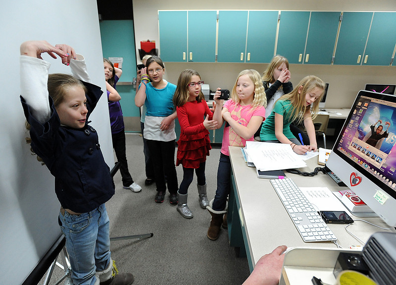 Aubrey Woodard, 9, acts siilly as she watches herself on a monitor Tuesday before delivering the local news on camera at Edmondson Elementary School in Loveland. The school received a creativity grant for 4th and 5th graders to put together a news cast for the school, called Stallion Scoop. Some students watch as others take video and pictures of her with iPods. Photo by Jenny Sparks