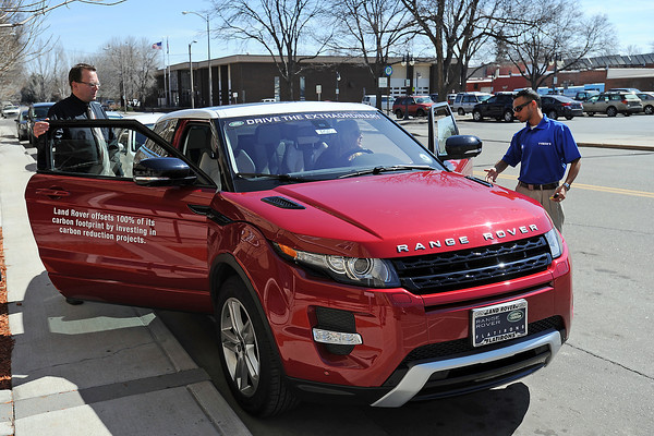 Land Rover Flatirons employee Fallon Price sits behind the steering wheel of a 2012 Range Rover Evoque as she explains its features to Nicholas Wacker, left, and Jake Howard during a stop in downtown Loveland on Wednesday of the Green Car Convoy.