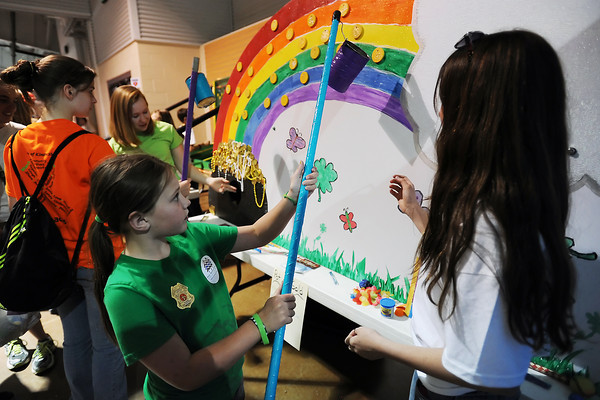 """Malorie Acott, 10, reaches up to pluck """"gold coins"""" off from a rainbow with the assistance of Fallon Stockley, 11, right, while playing the Lucky Clovers II 4-H Club's Pot of Gold game during the 4-H Carnival on Saturday, March 17, 2012 at The Ranch."""
