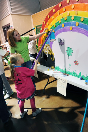 Kennedy Rhodes, 6, front, tries her hand at the Lucky Clovers II 4-H Club's Pot of Gold game with help from Jo Buckley, 15, during the 4-H Carnival on Saturday, March 17, 2012 at The Ranch.