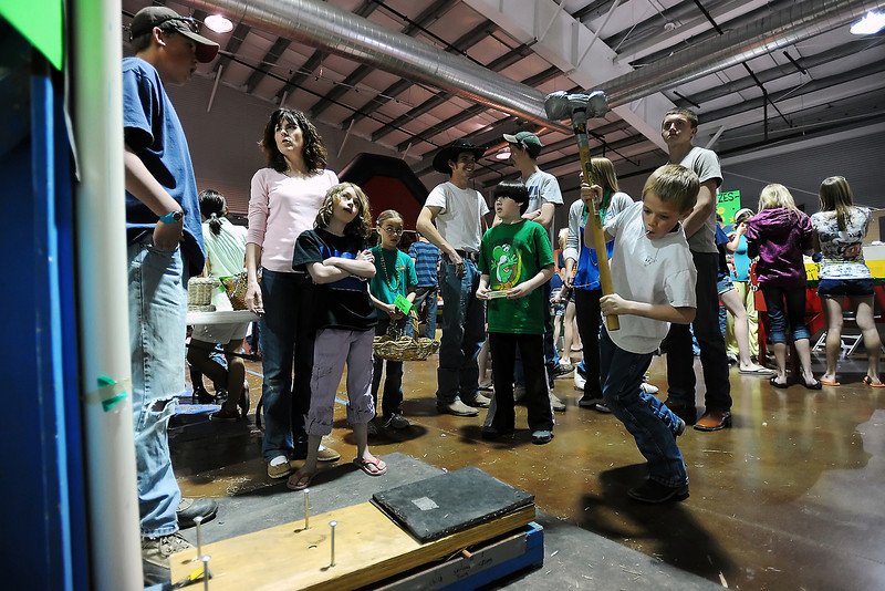 Dalton Williams, 10, front right, takes a swing with the sledge hammer at the North Forty 4-H Club's Bell Ringer game to try and win a prize during the 4-H Canival on Saturday, March 17, 2012 at The Ranch.