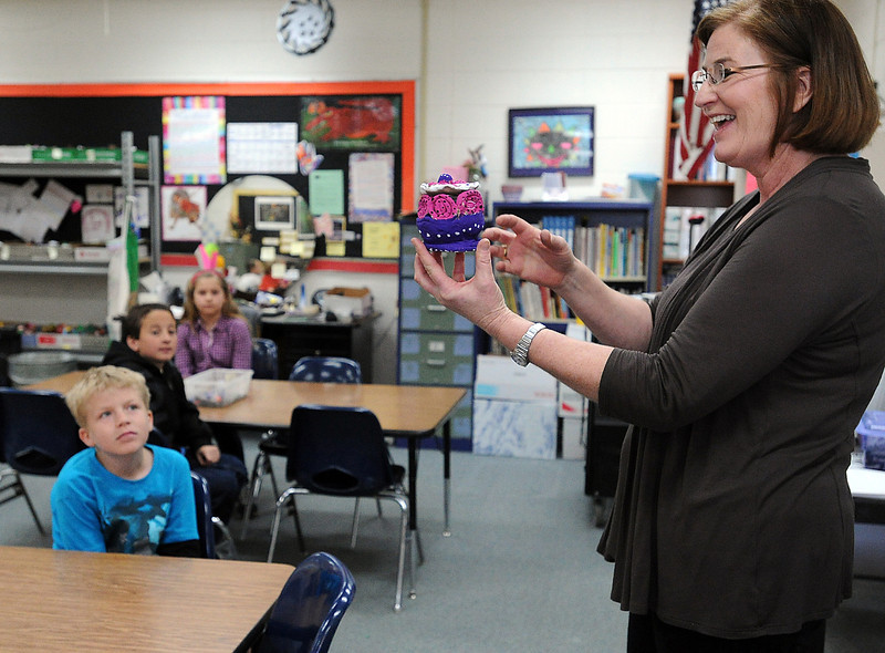 Namaqua art teacher Robyn Hall, right, holds a clay pot made by a student as she directs students to create a piece of artwork for their pot to rest on during class Wednesday at the school in Loveland. Hall also teaches art at Carrie Martin Elementary. Students in the background from front to back are Anthony Nelson, 9, Matthew Bellino, 9, and Madeline Madere, 10.<br /> Photo by Jenny Sparks