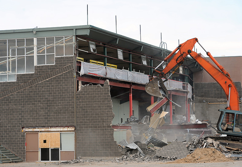 Crews work to demolish the old Cloverleaf Kennel Club Monday in Loveland. They started at the northeast side of the building and will work their way towards the south in the next couple of days in hopes that the huge windows on the south side of the building will block some of the dust from the Medical Center of the Rockies. Photo by Jenny Sparks