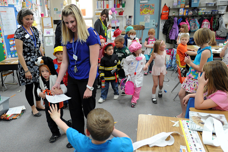 Early childhood teacher Ashley Hamand, middle, leads her preschool students through a first-grade classroom Wednesday afternoon while on a career march at Carrie Martin Elementary School. Youngsters dressed up in outfit showing their favorite careers as they paraded through several classrooms.
