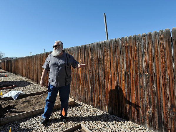 Tim Ward, a resident of the Sylmar Park community, stands in his backyard near a fence separating his home from a proposed Kum & Go gas and convenience store project that would be one of the region's largest. Residents on Monday will seek a Planning Commission ruling that would permit a 12-foot wall separating the community and the new developement. Photo by Jenny Sparks