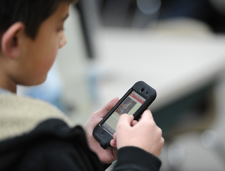 Edmondson Elementary School student Jacob Lucio, 10, uses an iPod to gather sports news for a news cast Tuesday during school. Photo by Jenny Sparks