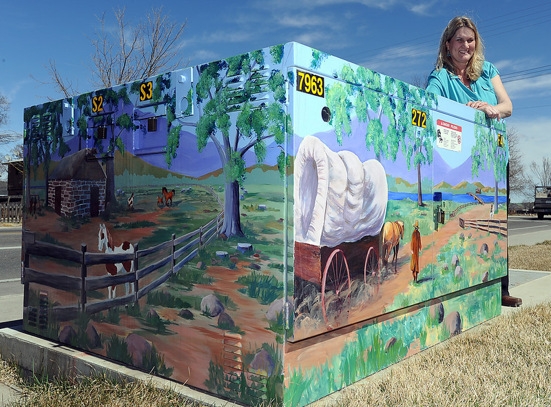 Loveland artist Mary Giacomini poses for a photo Wednesday by the transformer box she painted last summer at the corner of First Street and Madison Avenue. Photo by Jenny Sparks