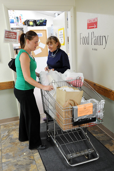 Berthoud resident April Clover, left, picks up a food basket from Linda Hollingsed on Thursday afternoon at House of Neighborly Service in downtown Loveland.