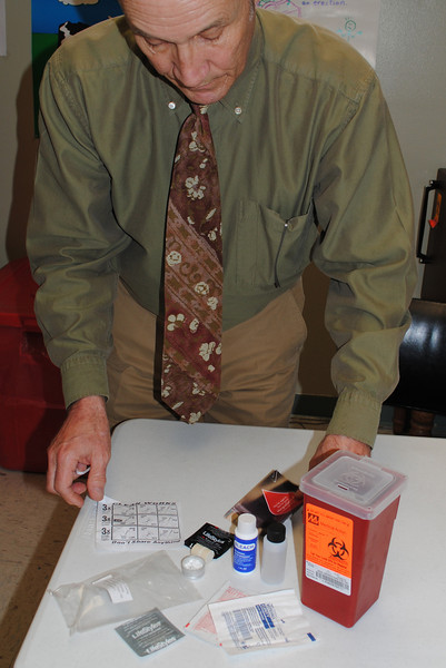 Jeff Basinger, director of the Northern Colorado Aids Project, displayes a needle bleaching kit and safe disposal container for intraveneous drug users - one of many ways the nonprofit tries to prevent the spread of HIV and Hepatitus C. The agency also provides access to rehabilitation and counseling.<br /> Reporter-Herald Photo/Pamela Dickman