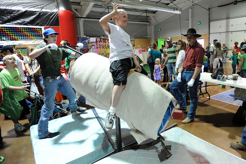 Ten-year-old Aaric Horve, middle, rides a mechanical bull powered by Rian James, 14, at the Owl Canyon Vaqueros 4-H Club's Bucking Barrell booth during the 4-H Carnival and Craft Show on Saturday, March 17, 2012 at The Ranch.