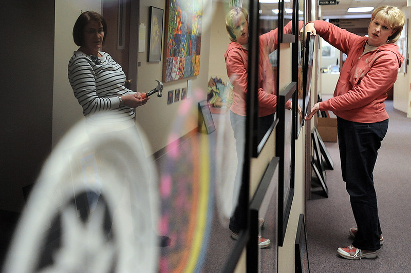 Thompson School District art teachers Robyn Hall, left, and Lora Patrick are reflected in framed artwork as the hang student pieces Friday for the upcoming annual art show at Aims Community College in downtown Loveland. Photo by Jenny Sparks