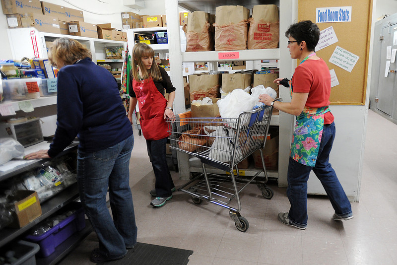 House of Neighborly Service employees, from left, Linda Hollingsed, Erin Becerra and Denise Moore fill food baskets for clients at the downtown agency.